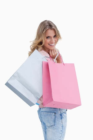 A woman looking back at the camera is carrying shopping bags over her shoulder against a white background photo