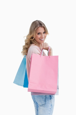 A woman who is carrying shopping bags is smiling at the camera photo
