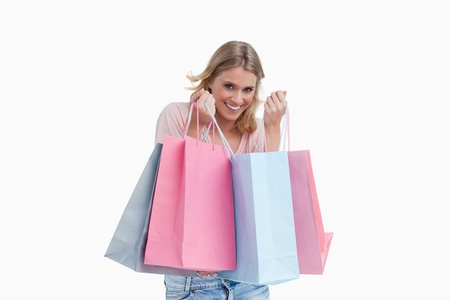 A smiling woman carrying shopping bags against a white background photo
