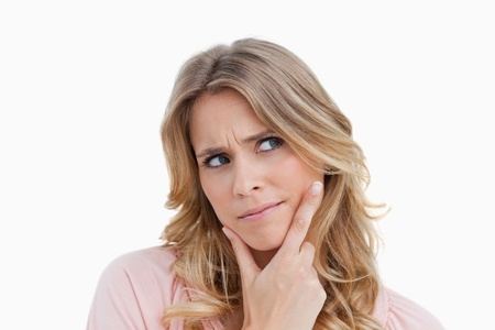 Seus young woman placing her fingers on her chin against a white background Stock Photo - 13673531