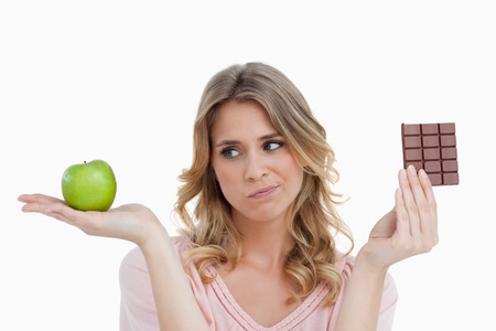 dudando: Pensativo mujer rubia joven dudando entre una fruta y chocolate Foto de archivo