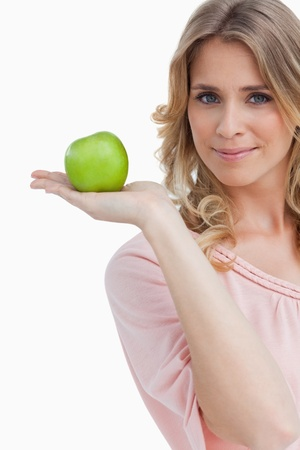 Woman holding an apple while looking at the camera against a white background photo