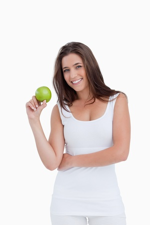 Smiling brunette woman holding a green apple against a white background Stock Photo - 13674280