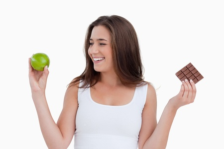 Smiling young woman looking at a green apple against a white background Stock Photo - 13674149