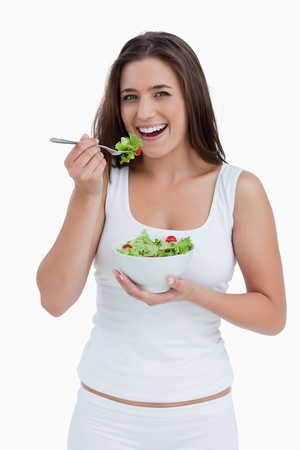 Smiling young woman eating a salad against a white background Stock Photo - 13674208