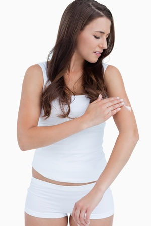 Thoughtful woman applying cream on her arm against a white background photo