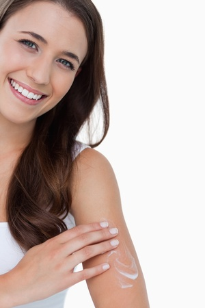 Smiling brunette woman looking at the camera while applying cream on her body photo