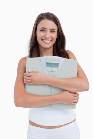 weighing scales: Donna sorridente con bilancia per pesare nei confronti di un background mentre
