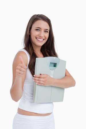 weighing scales: Sorridente donna bruna mettere i pollici mentre si tiene fino bilance