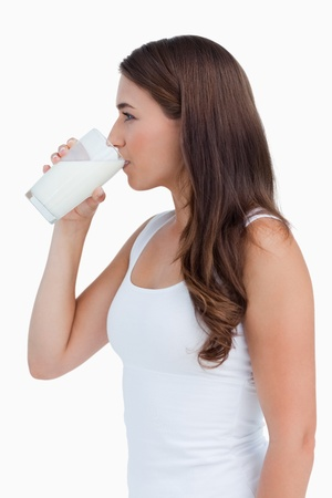 Side view of a young woman drinking a glass of milk against a white background photo
