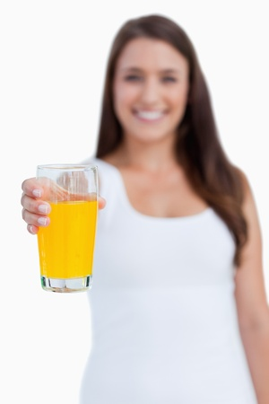 Glass of orange juice being held by a young woman against a white background photo