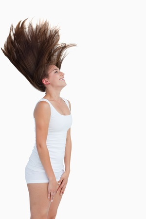 Smiling brunette flipping her hair against a white background Stock Photo - 13674737