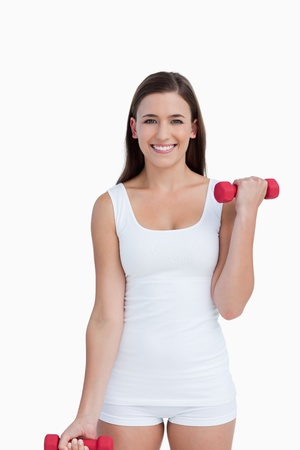 Attractive brunette holding red dumbbells against a white background Stock Photo - 13674393