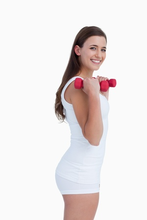 Side view of a young brunette holding dumbbells against a white background Stock Photo - 13674758