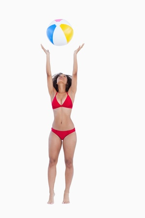 Attractive woman in bikini throwing a beach ball against a white background photo