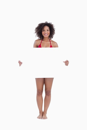 Smiling woman in beachwear holding a blank poster against a white background photo