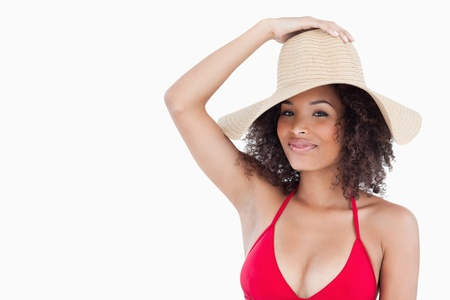 Attractive woman in swimsuit holding her straw hat against a white background photo