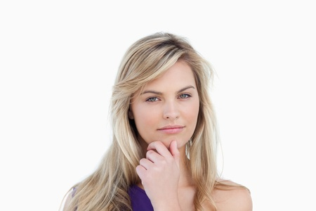 Serious blonde woman looking at the camera against a white background Stock Photo