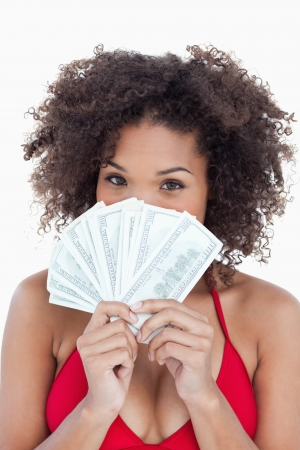 Brunette woman hiding her face behind a fan of notes against a white background photo