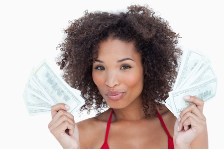 puckering: Attractive brunette woman puckering her lips while holding a fan of bank notes Stock Photo