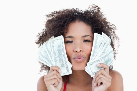 puckering: Brunette woman puckering her lips while holding two fans of bank notes Stock Photo