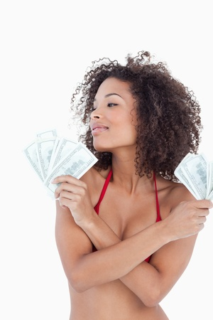 Young attractive woman looking away while holding two fans of bank notes photo