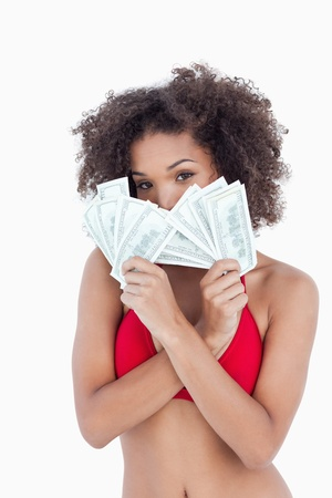 Brunette woman hiding her face behind two fans of notes against a white background Stock Photo - 13672590