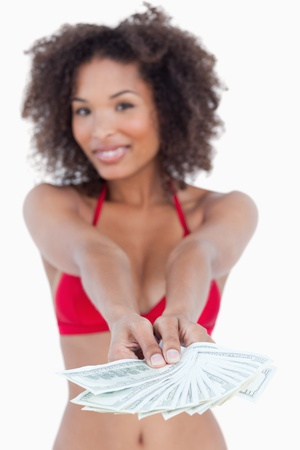 Fan of notes being held by a young woman against a white background Stock Photo - 13673356
