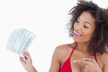 Smiling brunette woman pointing a fan of dollar notes against a white background photo