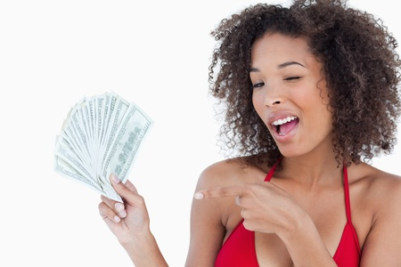 Young woman blinking an eye while holding dollar notes against a white background photo