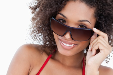 Smiling young brunette looking over her sunglasses against a white background Stock Photo - 13671206