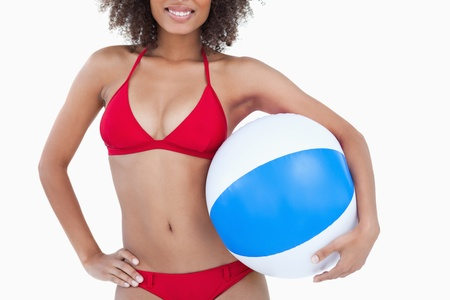 Smiling brunette woman holding a beach ball against a white background photo