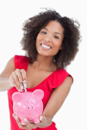 Pink piggy bank being given bank notes against a white background photo