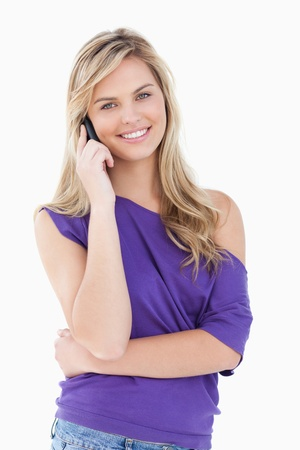 persona llamando: Feliz mujer rubia con su tel�fono celular contra un fondo blanco Foto de archivo