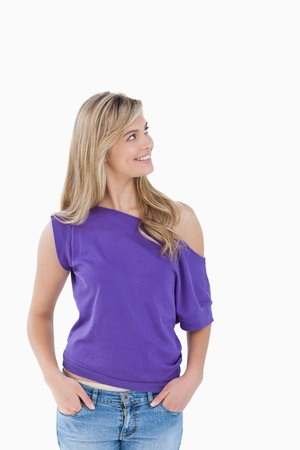 Smiling blonde woman looking away against a white background