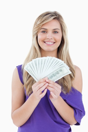 Happy blonde woman holding a fan of notes against a white background photo