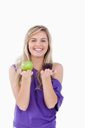 dudando: Mujer rubia feliz dudando entre una magdalena y una manzana verde
