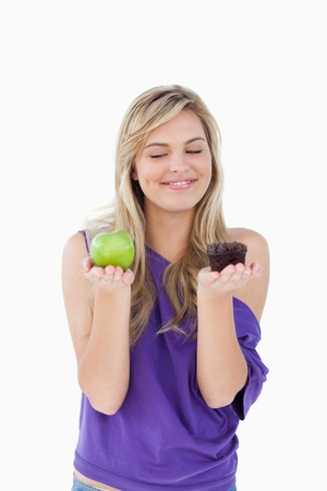Smiling blonde woman holding a fruit and a muffin against a white background Stock Photo - 13674113