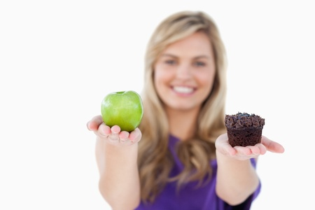 A fruit and a muffin being held by a blonde woman against a white background photo