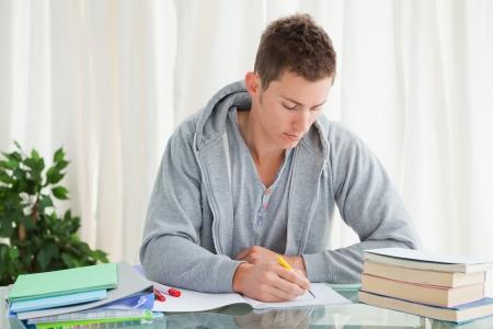 Studente maschio di fare i compiti nella sua casa