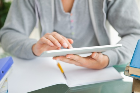 Close-up of a student using a touch pad while doing his homework photo