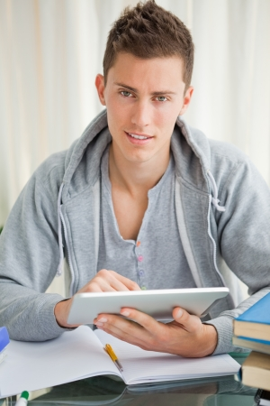 Handsome student using a touch pad while doing his homework photo