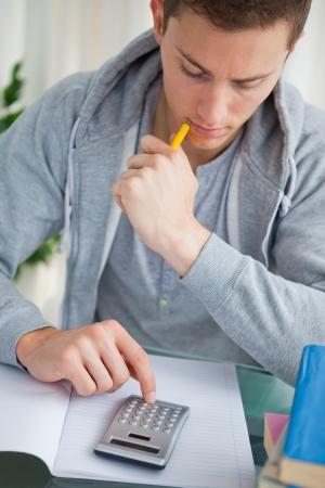 Student using a calculator while doing his homework photo