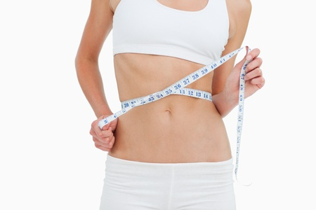 Close-up of a woman on diet measuring her waist against white background photo