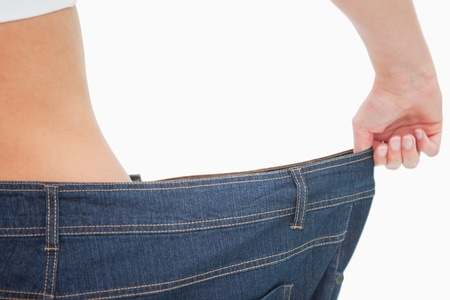 Close-up of a woman waist in a too big pants against white background photo