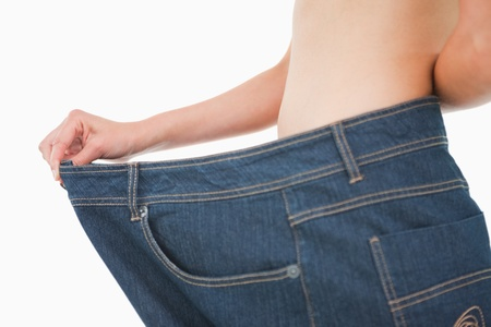 Close-up of a woman belly in a too big pants against white background photo