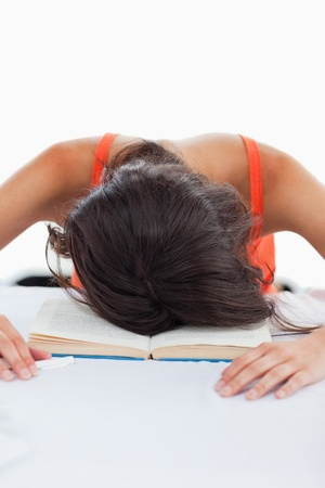 Depressed student head on her books against white background photo