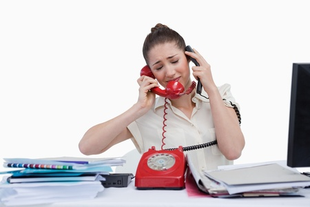 overburden: Overburden businesswoman answering the phones against a white background Stock Photo