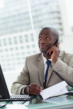 Portrait of a happy entrepreneur making a phone call while reading a document in his office Stock Photo - 13799854