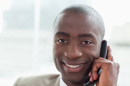 Close up of a smiling businessman on the phone in his office photo